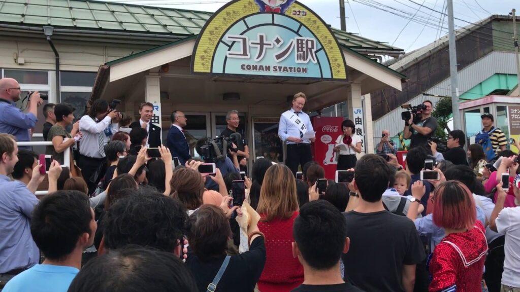 conan o'brien speaks in front of a crowd in hokuei